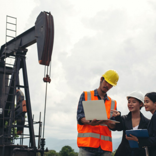 engineering-team-stands-beside-working-oil-pumps-with-sky_1150-19224