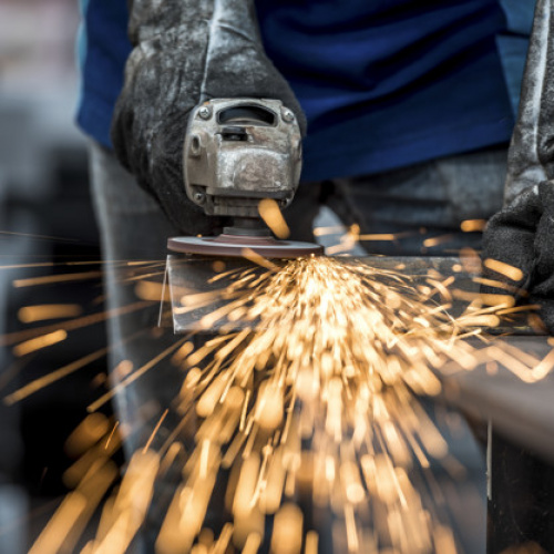 Industrial worker cutting metal with many sharp sparks
